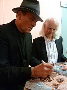 Eric Andersen (links) signiert den Ausstellungskatalog von Oliver Jordan (rechts), dem seine Camus-Songs als CD beiliegen. ©Foto: Anne-Kathrin Reif